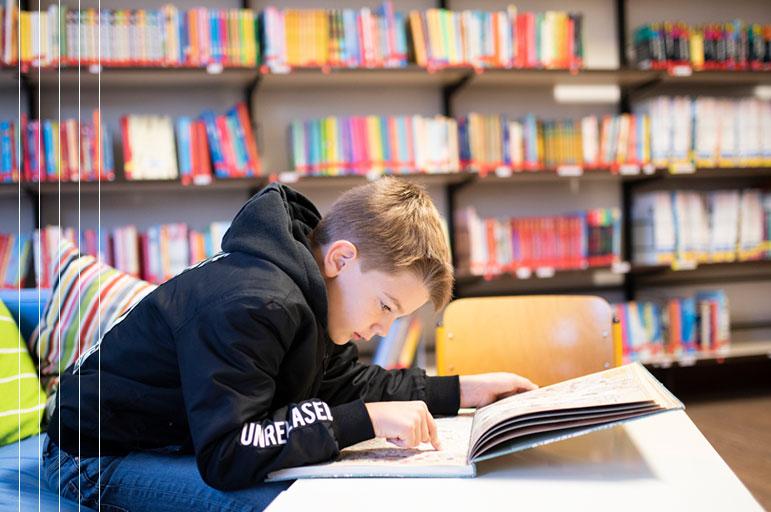 Schüler liest in der Bibliothek